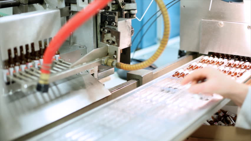 Robotic arm lifting ampules at packaging line in pharmaceutical factory.