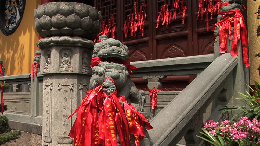 Stone lion with a mouth full of prayer ribbons at Jade Buddha Temple, Shanghai, China, zoom in  - HD stock footage clip