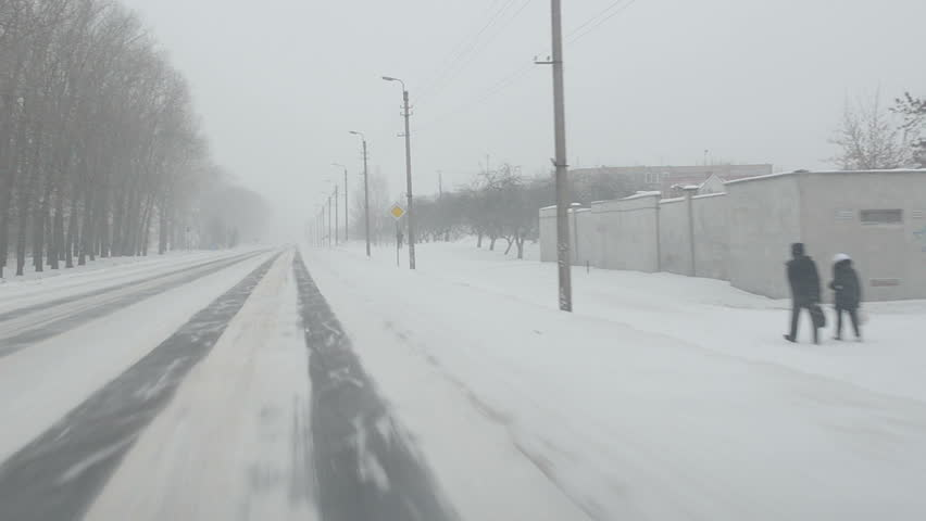 car go on road near small town and snowstorm snow falling. people walk. front car window view. - HD stock video clip