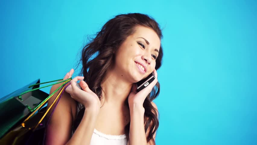 young woman with packages talking on the phone