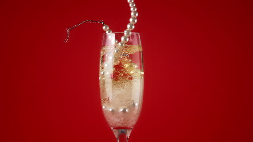 Pearl necklace falling into champagne flute in slow motion