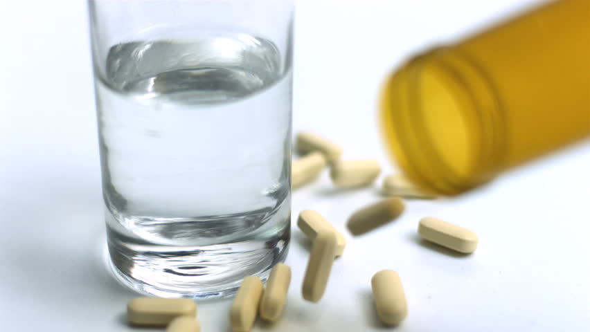 Pills pouring from jar beside glass of water in slow motion