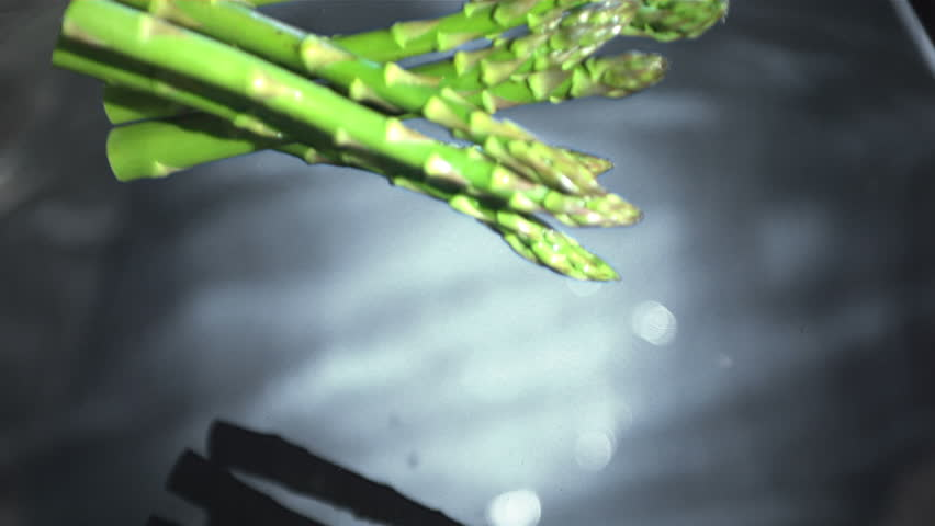 Asparagus stalks falling into water in slow motion