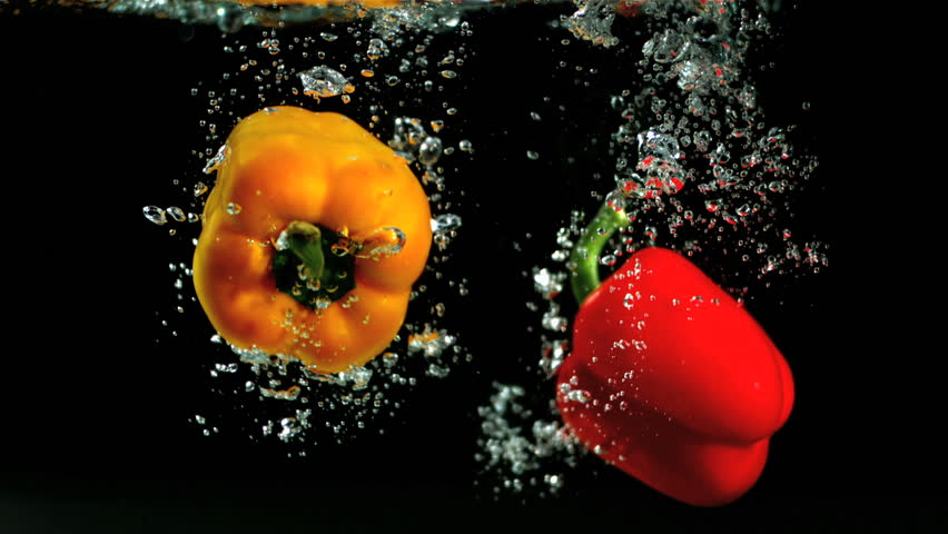 Two peppers falling in water and floating in slow motion