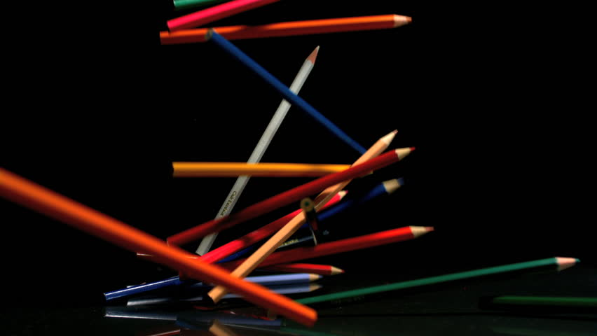 Colouring pencils falling on black background in slow motion