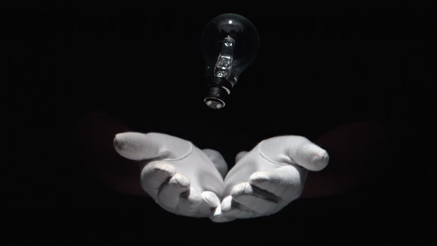 Gloved hands throwing and catching a lightbulb in slow motion