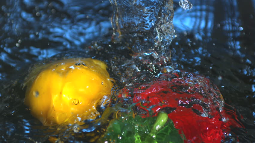 Three peppers falling into water in slow motion
