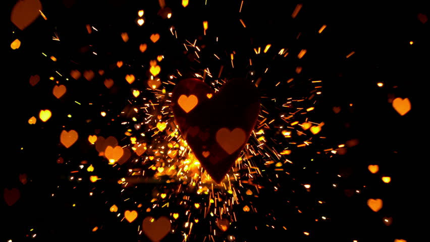 Golden confetti and sparks flying against heart in slow motion