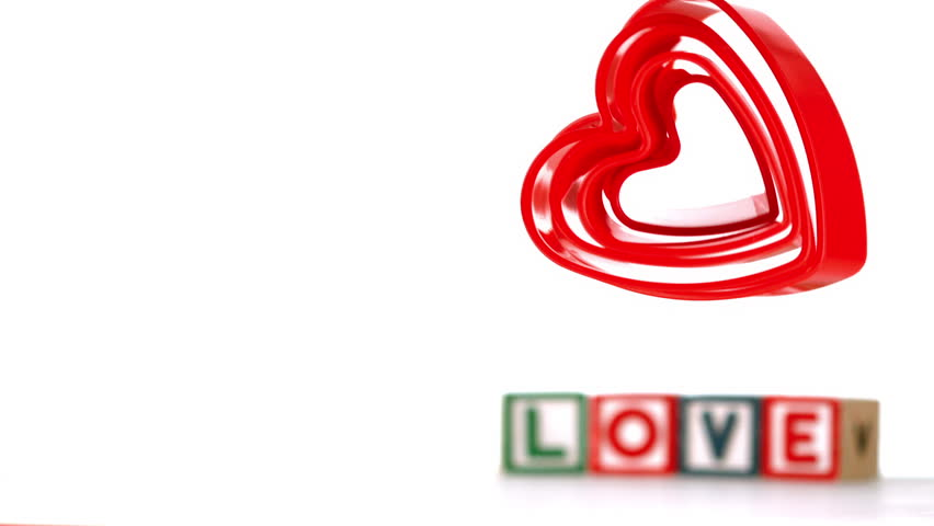 Heart ornaments falling with blocks spelling love in background in slow motion - HD stock video clip