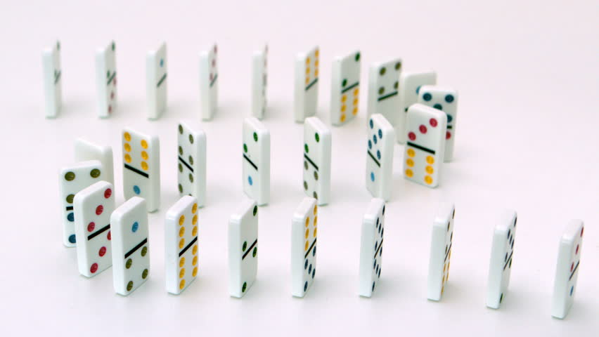 White dominoes falling over in slow motion
