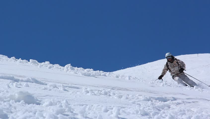 Skier close-up in soft snow on a sunny give against the clear sky