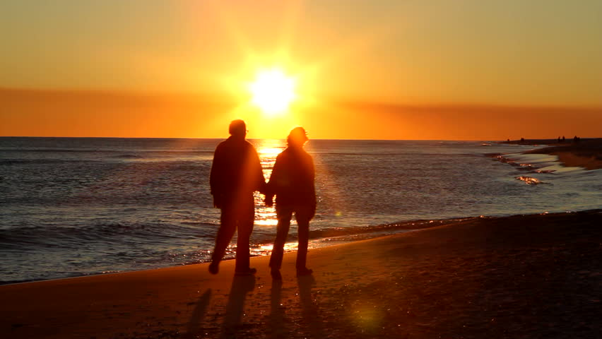 Senior adult couple holding hands walk up the beach as the sun is about to set on the horizon. - HD stock footage clip