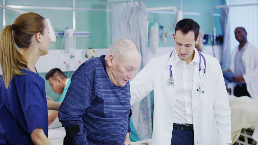 An attractive and caring young doctor and nurse help an elderly male patient to walk. Other doctors and nurses can be seen attending to other jobs in the background. In slow motion. | Shutterstock HD Video #3432413