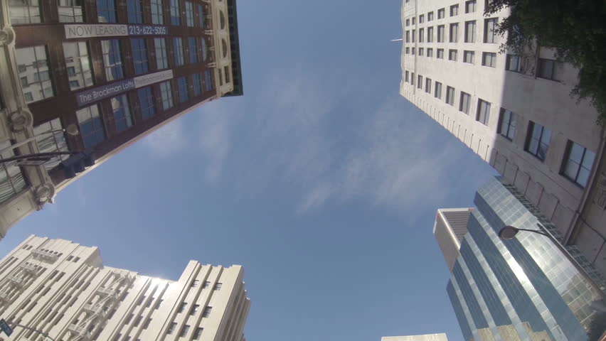 Shot in slow motion at 60fps through downtown Los Angeles looking up at the buildings.  POV with flare  #3456164