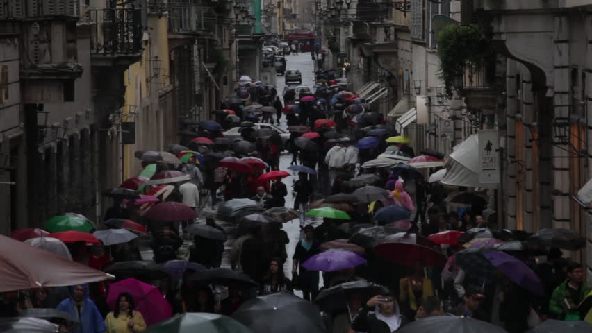 Hundreds of tourists holding umbrellas walking down Via dei Condotti