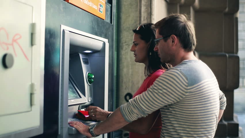 Young couple withdrawing money from an ATM, steadycam shot  - HD stock video clip
