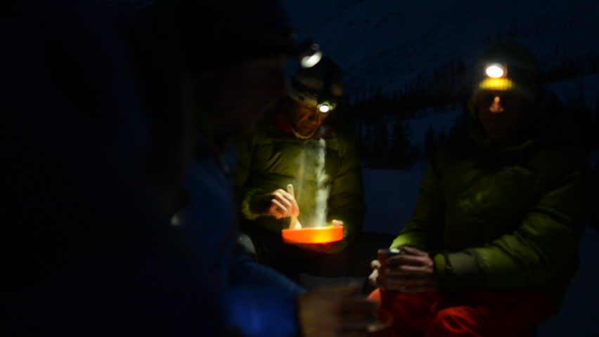 A group of climbers in the Alaskan wilderness prepare a late dinner in the snow at night over a camping stove