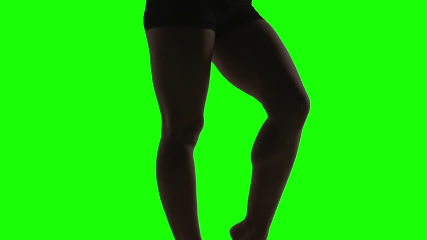 Silhouette of a young woman dancing in front of green screen, legs | Shutterstock HD Video #3463085
