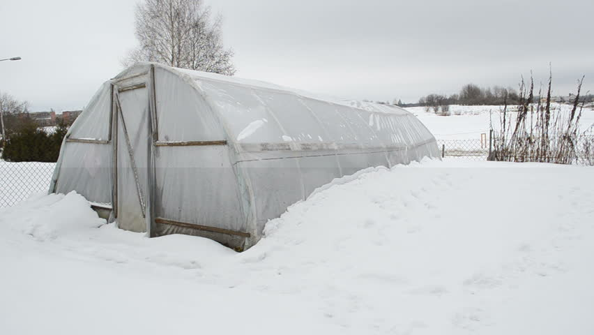 panorama view of wooden diy homemade greenhouse covered with polythene and snow in winter garden. snow falling. - HD stock video clip