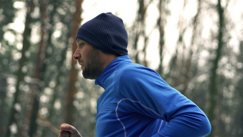 Lone runner in wintry wood, slow motion shot at 240fps  - HD stock video clip