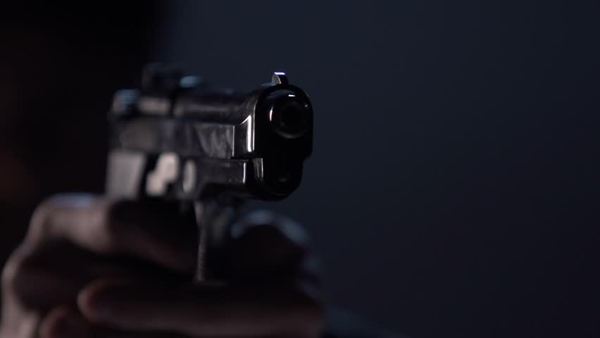 Close up of 9 mm handgun. Shooter takes three shots