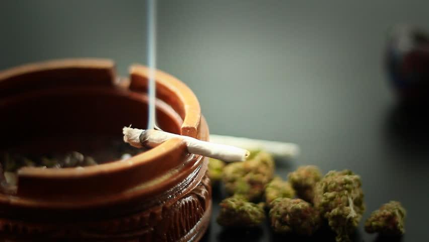 Marijuana Joint Burning 1. A marijuana filled joint burning on the edge of a wooden ashtray. More marijuana to the side.