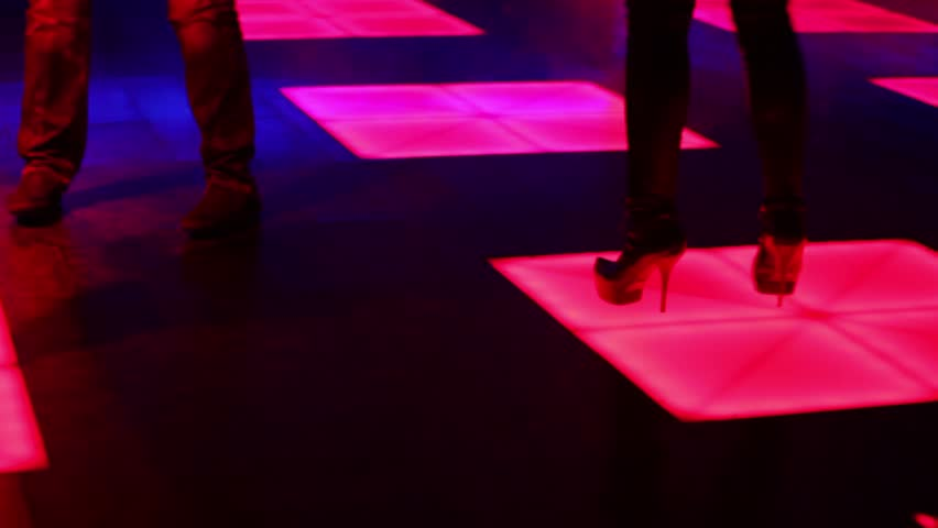 Three women and one man dance in night club, shown in motion with only legs visible - HD stock video clip