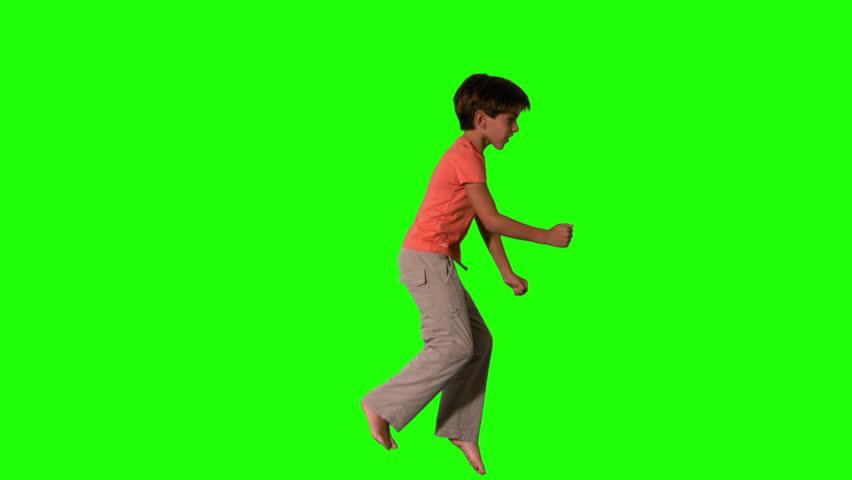 Boy jumping on green screen side view in slow motion | Shutterstock HD Video #3497276
