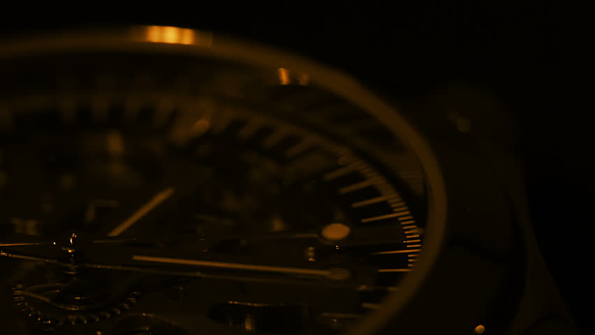 Watch close up. The light source moves around the watch. Tinted in gold