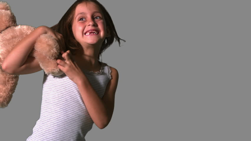 Little girl twirling and catching teddy on grey background in slow motion - HD stock video clip
