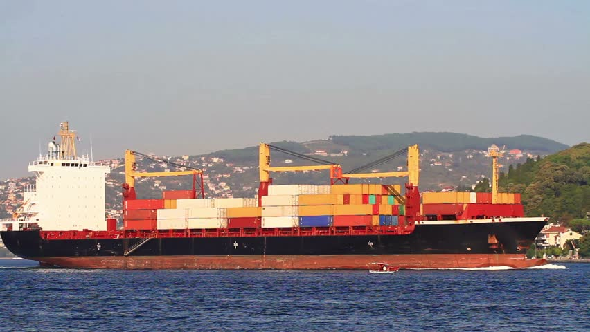 A large container ship full of cargo sailing along the shore