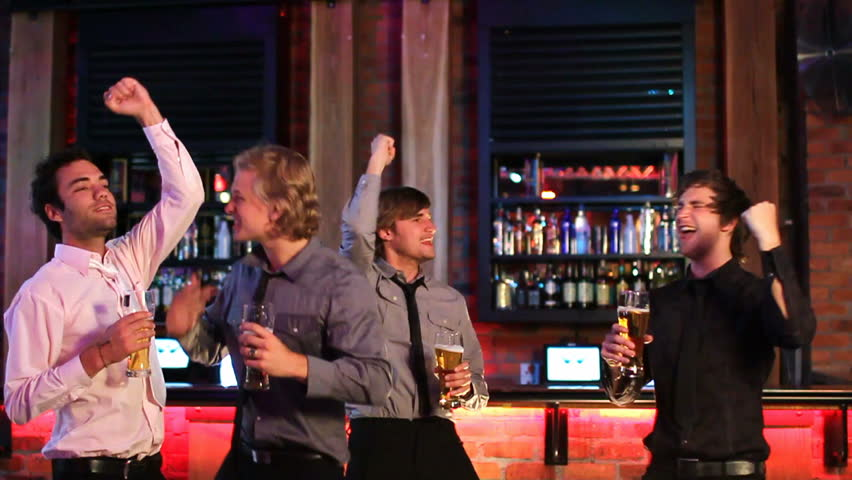 Friends /businessmen watching a sports game in a bar cheering at a score in slow motion. - HD stock video clip