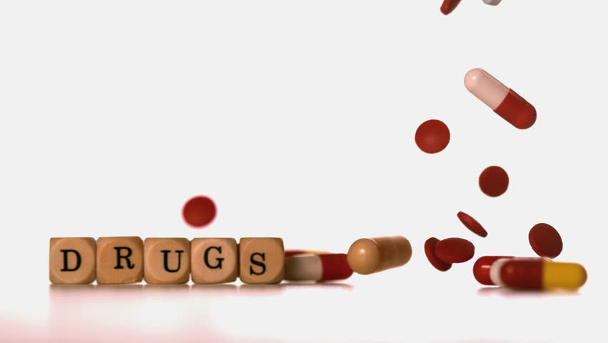 Different tablets falling beside dice spelling drugs in slow motion - HD stock footage clip