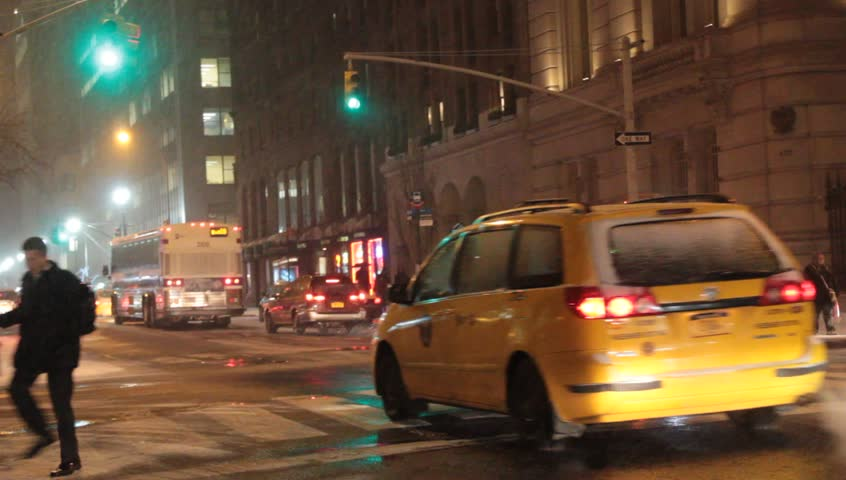 New York, NY - Circa 2012: Night traffic in Snow Fall during a blizzard with cabs and buses speeding down the street - HD stock footage clip
