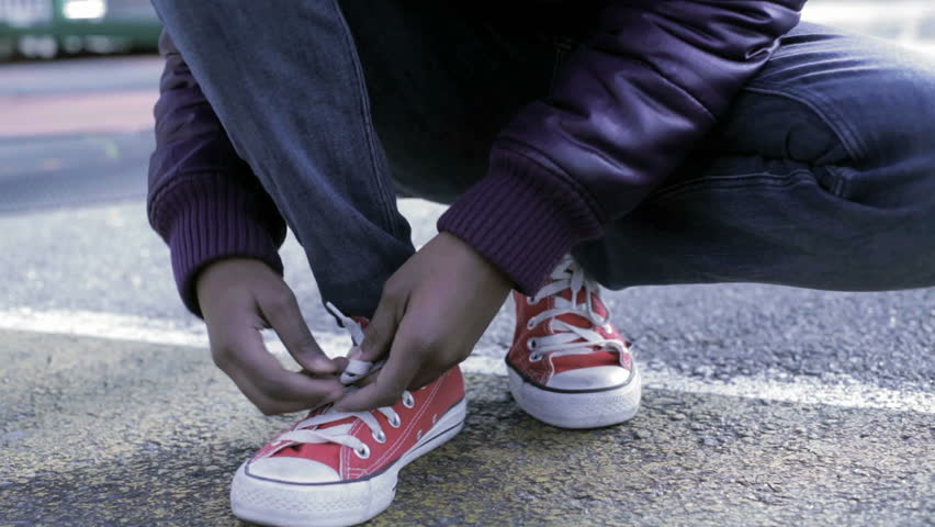 African American Black Kid tying shoe in the park getting ready to run - HD stock video clip