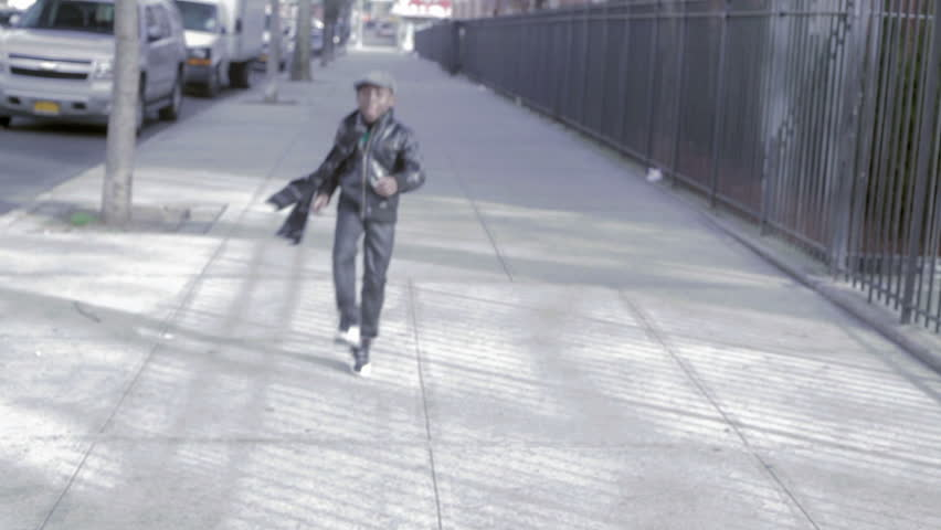 African American Black kid with hat skipping outside in the street in the day