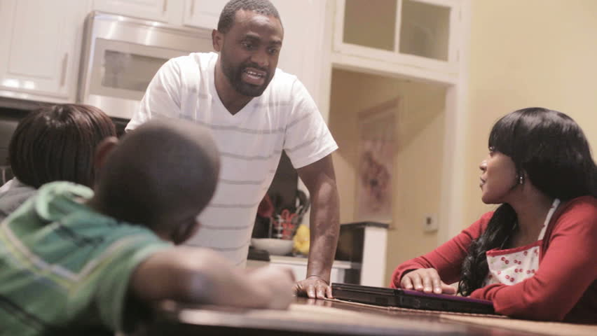 African American Black Family talking at dinner table in the kitchen. father is telling a story to his son and daughter.