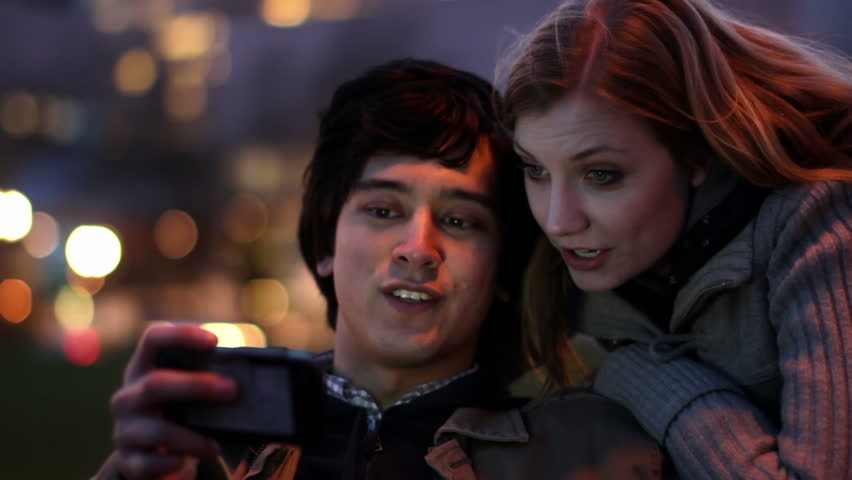 Smart Phone Couple at Night.  Attractive young couple laugh as they find content