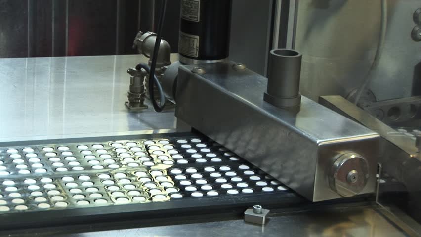 Automated production of medicines. Creating a pill. Tablets on the conveyor