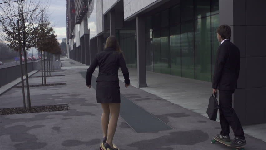 Businessman and businesswoman long board skating in big city - HD stock video clip