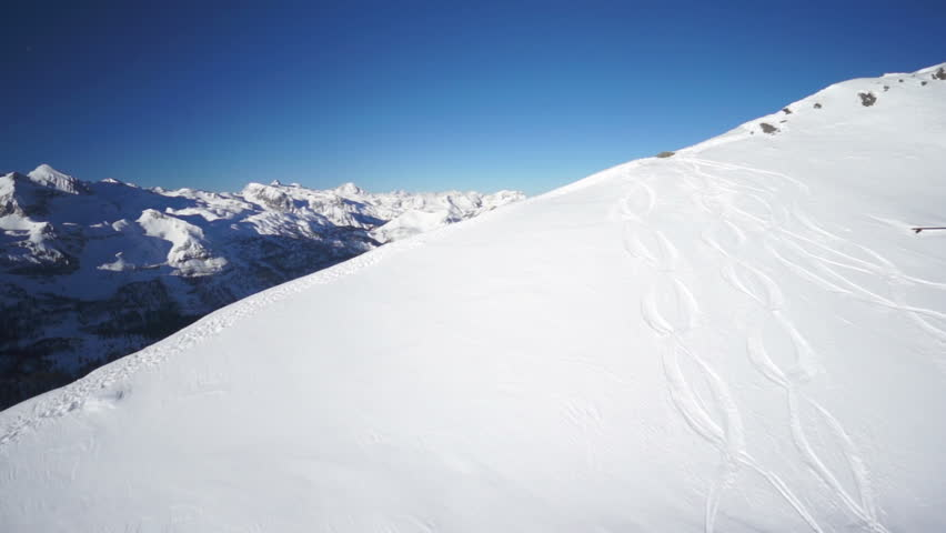 aerial view snow covered mountains, mountain ridge and panorama on beautiful winter day with blue sky