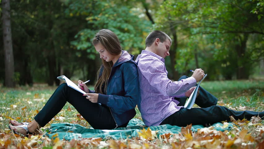 Teenage students studying in autumn park - HD stock video clip