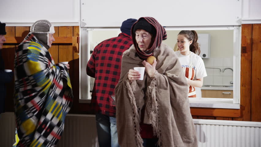 Voluntary workers standing at a soup kitchen serving hatch are handing out cups of hot soup and bread to a waiting line of homeless and needy people. In slow motion - HD stock video clip
