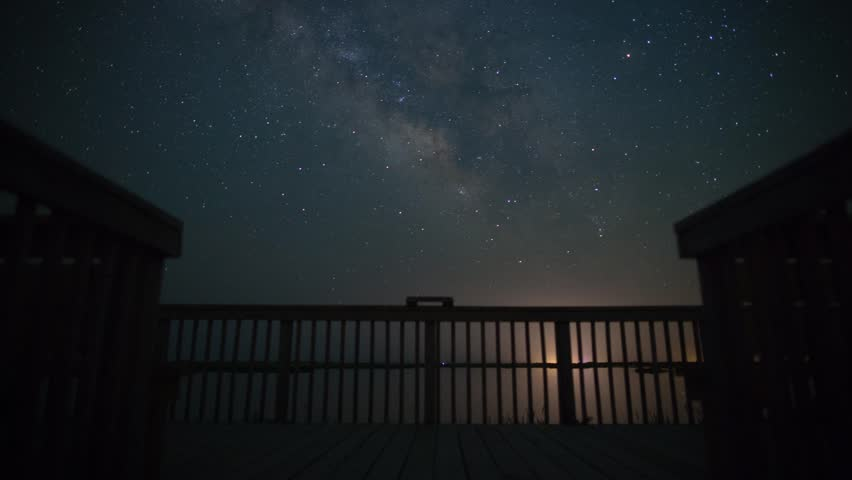 Milky Way + stars motion time-lapse with deck, car headlights, water