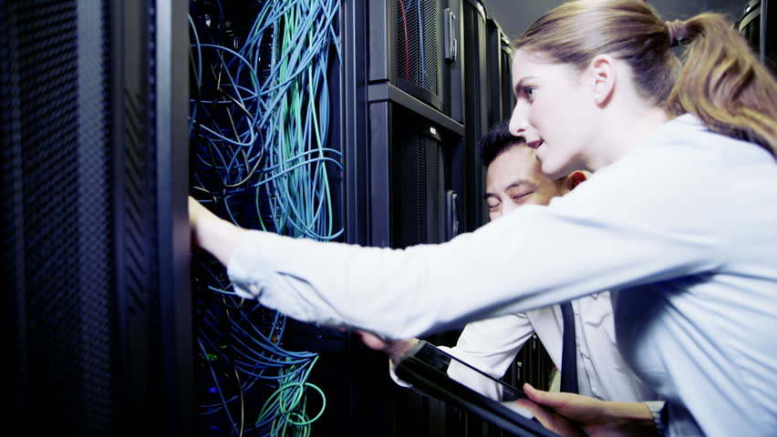 One male and one female engineer of mixed ethnicity are working in a data center with rows of server racks and super computers. They are checking all of the equipment. In slow motion.