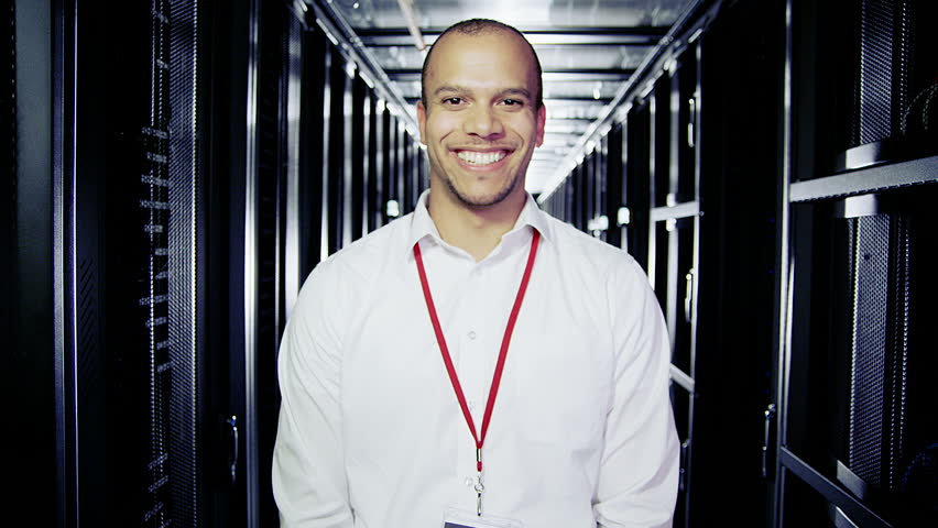 Portrait of a male IT engineer who is working in a data center with rows of server racks and computers.  #3589283