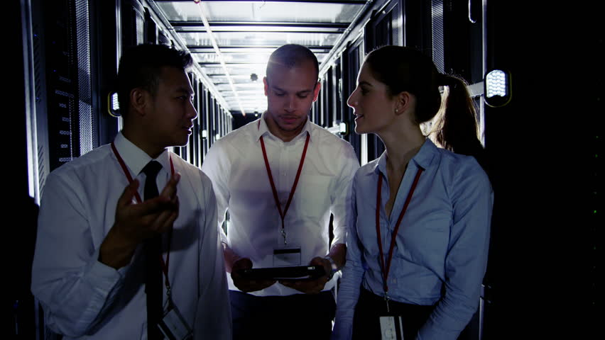 Team of people working in a data center with rows of server racks and super computers. They are looking into data cabinets and checking cables and other equipment.