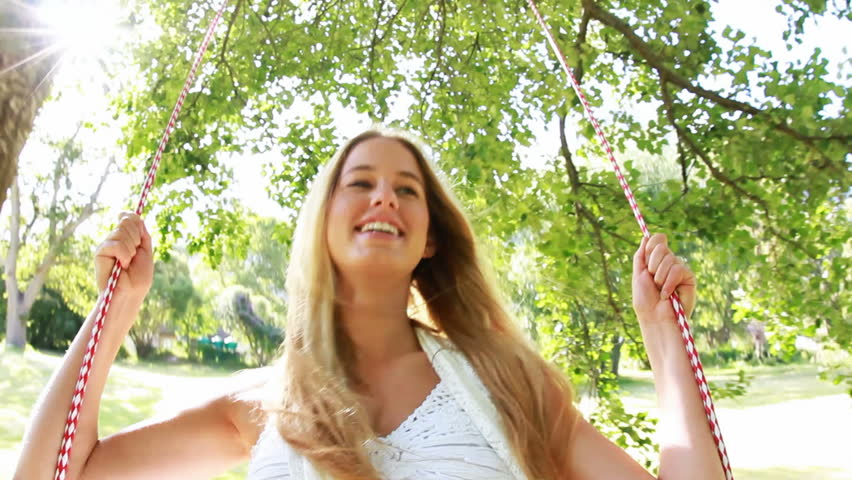 Young beautiful woman is having fun on a swing underneath a tree in nature. - HD stock footage clip