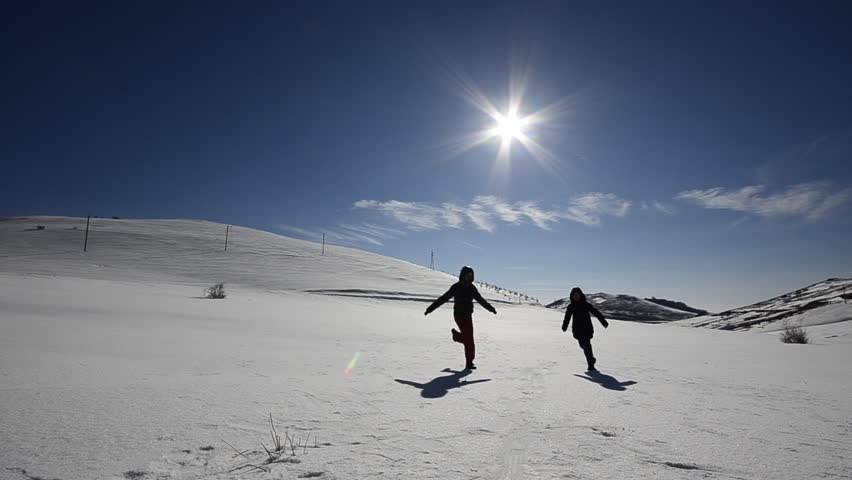 Two kids boy and girl enjoying play run on snow slope. Girl runs toward camera,