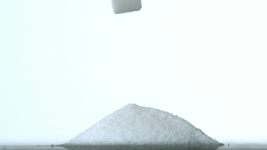 Sugar cubes falling into pile of sugar in slow motion